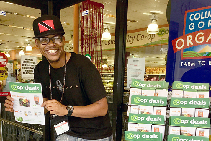 A co-op employee shows off great deals in the Co+op Deals flyer