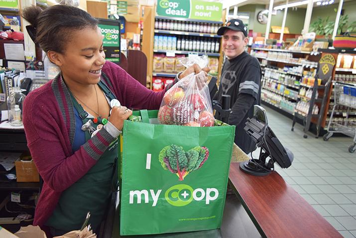 Cashier at food co-op bagging groceries