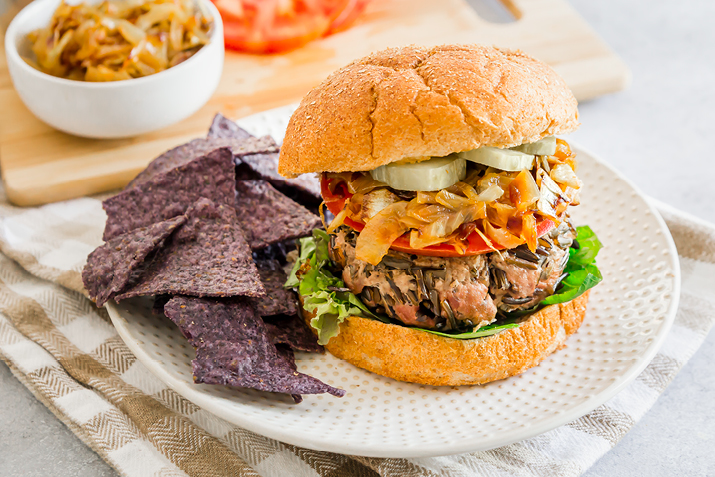 Wild Rice Beef Burger plated with blue tortilla chips on the side