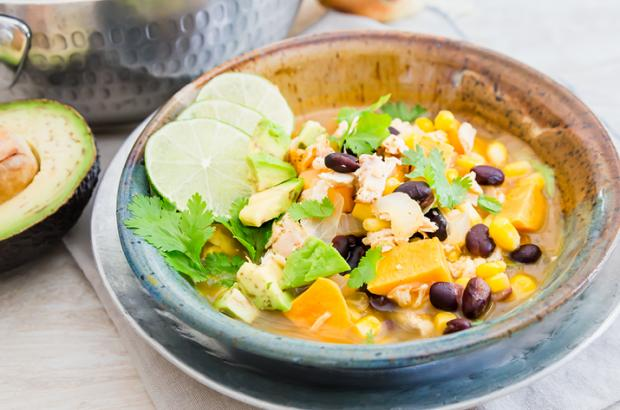 Bowl of Chipotle Lime Chicken and Veggie Soup with beans, sweet potatoes and lime wedges