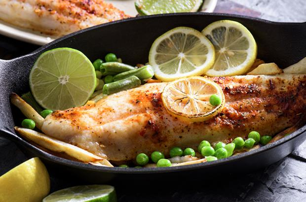 Cooked Cajun freshwater fish in a skillet with peas and lemon