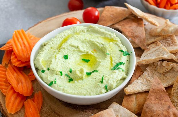 Bowl of green hummus with baked pita chips