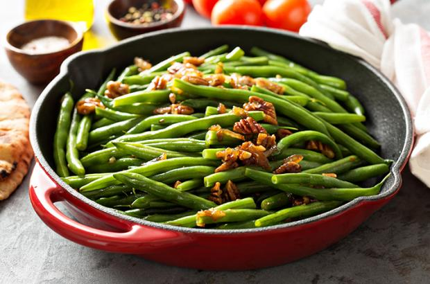 Sauteed green beans in a skillet with candied pecans
