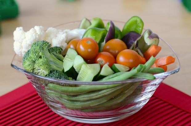 Bowl of veggies with toys scattered around