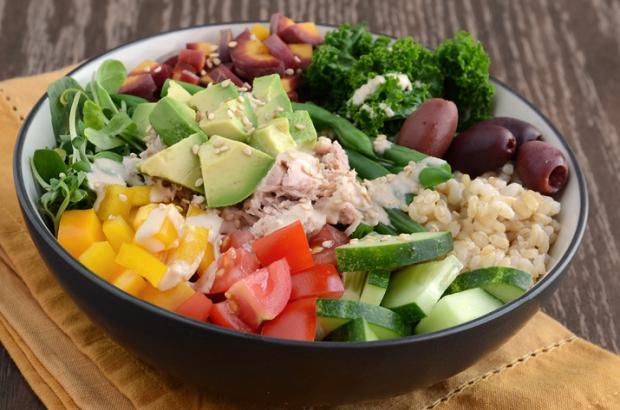 Healthy Buddha-style bowl with veggies, brown rice, tuna and tahini dressing