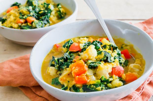 Two bowls of hearty, red lentil stew with kale on a table