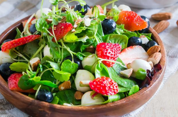 Colorful salad in a bowl with strawberries, blueberries, mozzarella ball slices and spring greens