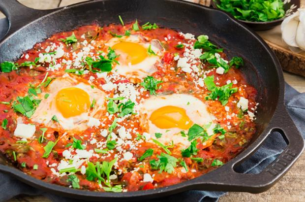 Shakshuka with spinach in a cast iron pan