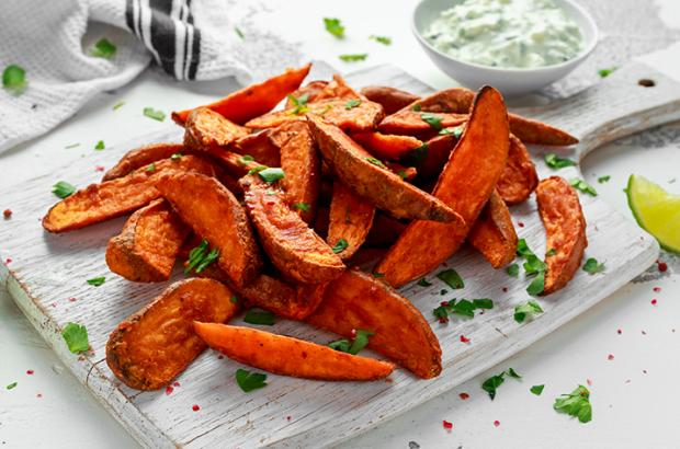 Spicy Sweet Potato Wedges on a Cutting Board with Jalapeno Sour Cream