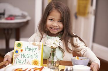 Child holding tray of food and card for Mother's Day