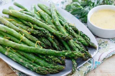 Charred asparagus on a platter with tarragon aioli