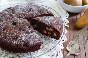 Chocolate pear cake with nuts with a slice pulled out