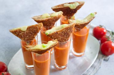 Small glasses of tomato soup topped with a grilled brie sandwich wedge