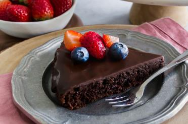 Slice of luscious flourless chocolate cake with ganache topped with berries