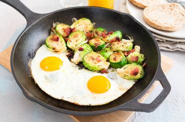 Cast iron pan with Brussels sprouts, bacon, two eggs with English muffins on the side