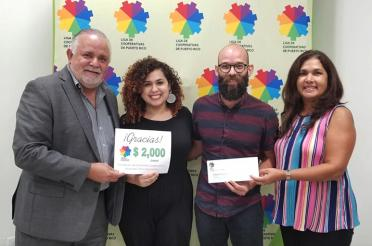 La Liga de Cooperativas of Puerto Rico accepts a donation check from food co-ops
