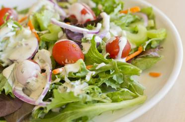 Salad on a plate topped with white ginger jalapeno dressing