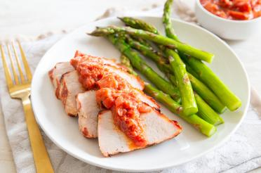 Grilled Pork Tenderloin with Rhubarb Barbecue Sauce plated with steamed asparagus