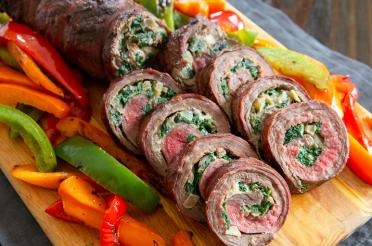 Rolled grilled flank steak with spinach and blue cheese