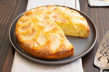 Whole Italian pear cake, with a wedge on a plate