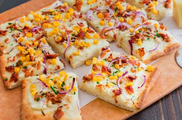 Mashed Potato and Bacon Pizza sliced on a cutting board