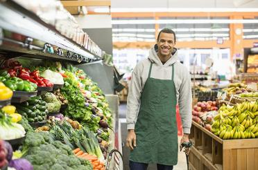 Smiling co-op staff person in the produce aisle ready to spray the produce