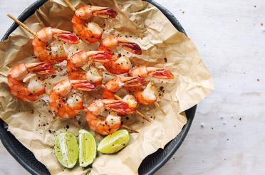 Grilled shrimp on skewers with a lime wedge