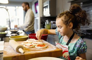 Girl making homemade pizzas with dad in the background