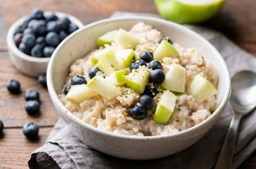 Bowl of oatmeal with apples, blueberries and sesame seeds