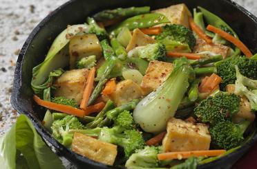 Cast iron skillet with broccoli, bok choy, tofu, carrot stir-fry