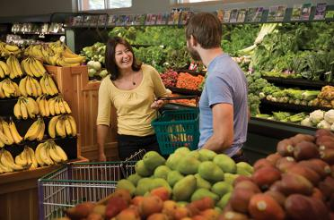 Two shoppers share a laugh while shopping at a food co-op