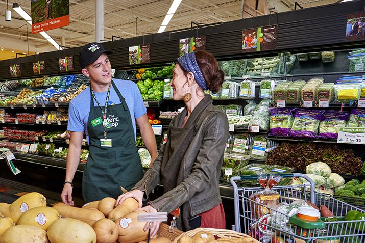 A staff person chats with a shopper in the product department at a food co-op