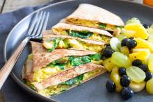 Quesadillas wedges stacked on a plate with a side of fruit salad