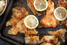 Cooked, spiced catfish fillets on a baking tray