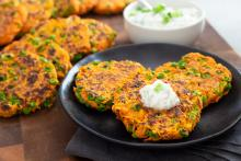 Carrot-Pea Fritters on a plate with a dollop of raita