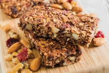 Stacked Chewy Cocoa Granola Bars on a cutting board