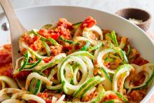 Zucchini noodles on a plate topped with lentil Bolognese sauce