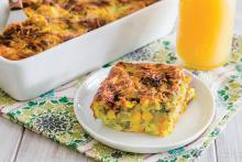 Square of vegetable egg bake on a plate next to casserole dish