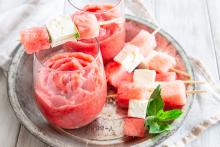 Watermelon Mint Frosé in a glass, served with watermelon and feta skewers