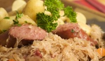 Bavarian food prepared in the spirit of Oktoberfest and the fall seasona: kielbasa (sausage), boiled, parsley potatoes, sauerkraut baked in savory sauce and flavored with smoked backon, caraway seeds, carrots and onions.